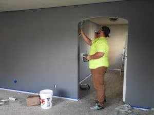 A person having an easy time painting a doorway because they are aware of the home improvement dos and don'ts.